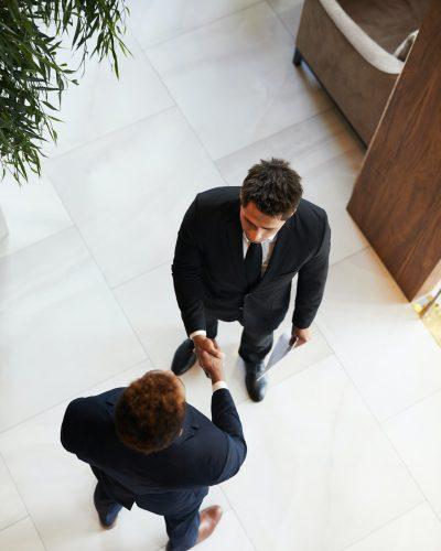 Confident entrepreneurs making handshake in lobby